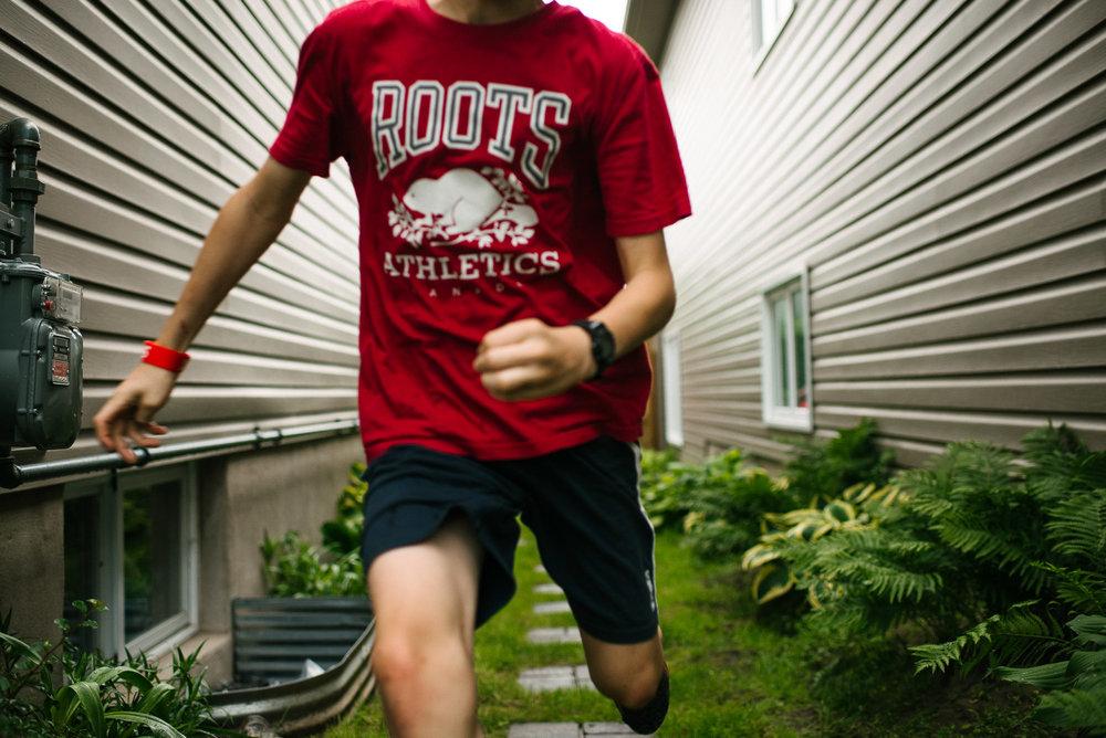 boy with red shirt runs toward camera