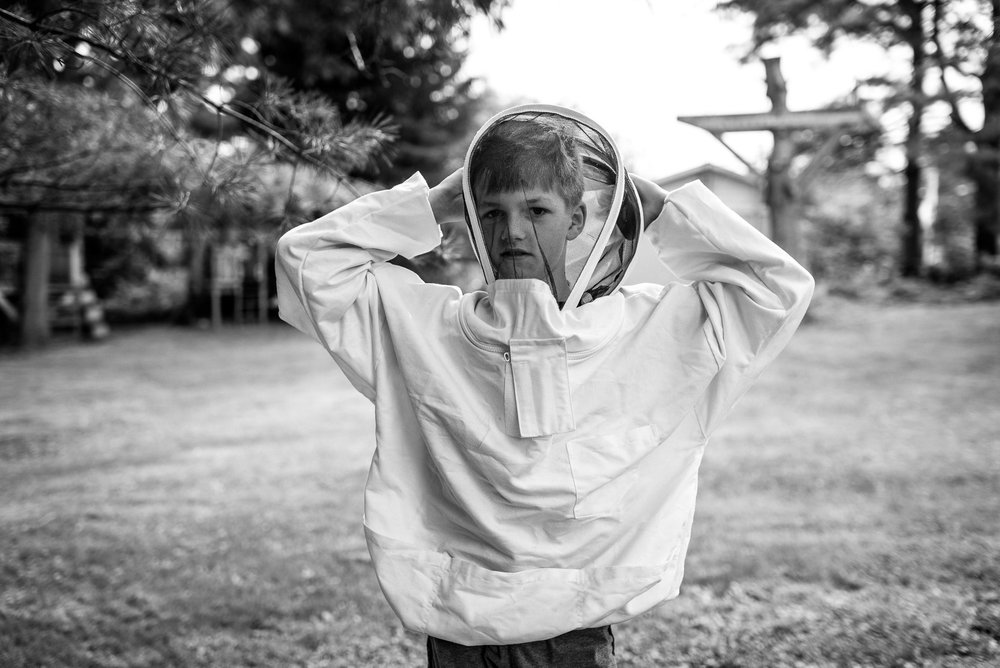boy wears a beekeeping outfit