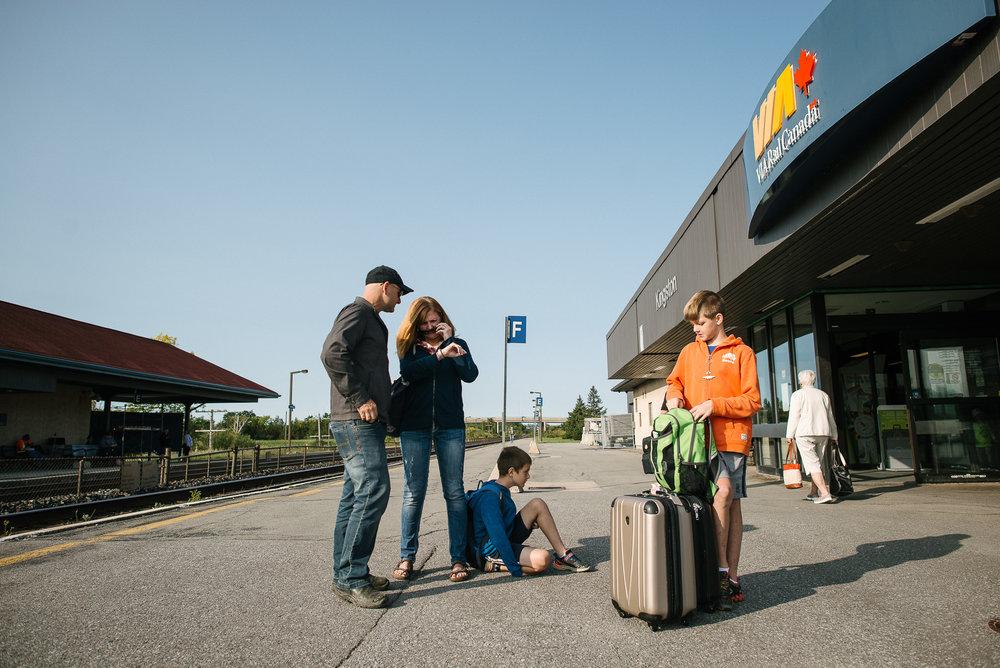 family waits at a train station