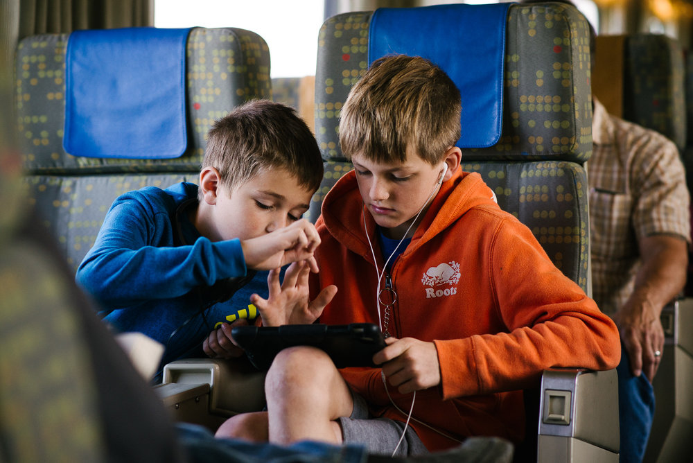 boys look at a game pad on a train