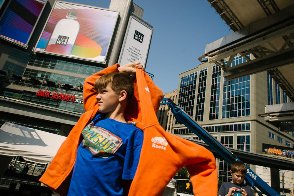 Boy with orange hooded sweatshirt stands in Dundas Square