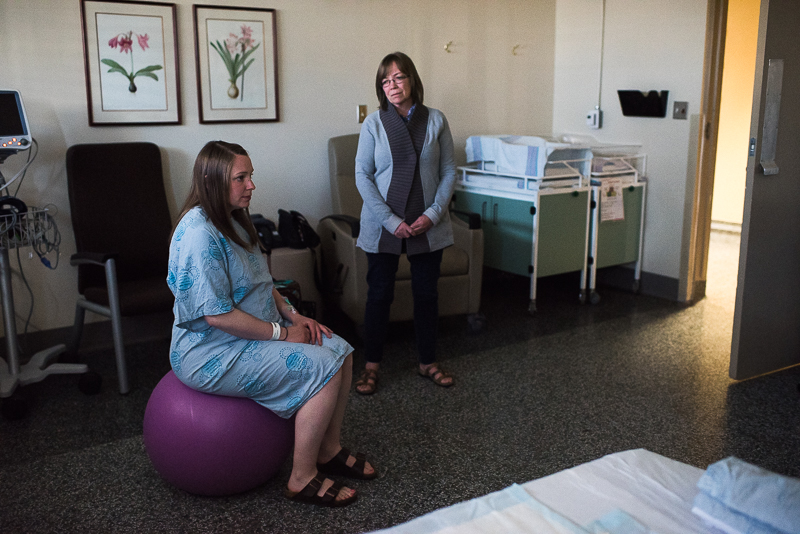 labouring mother sits on inflatable ball as her mother watches her in hospital delivery room