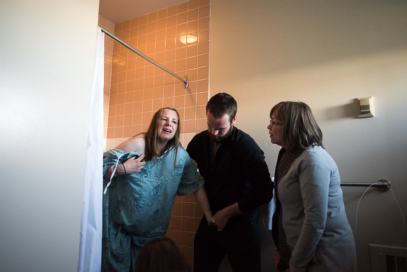 husband and mother help labouring woman exit the shower during a painful contraction