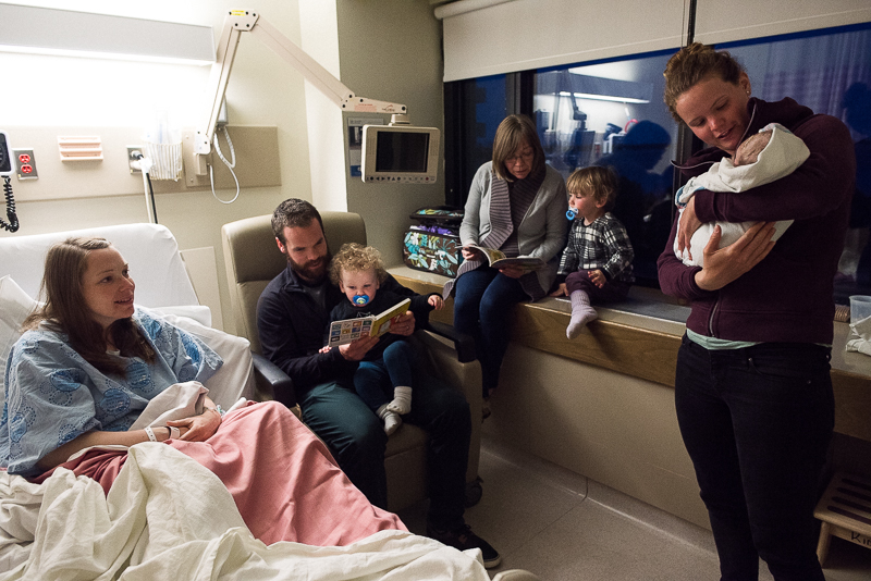 family gathers in hospital room to welcome newborn baby