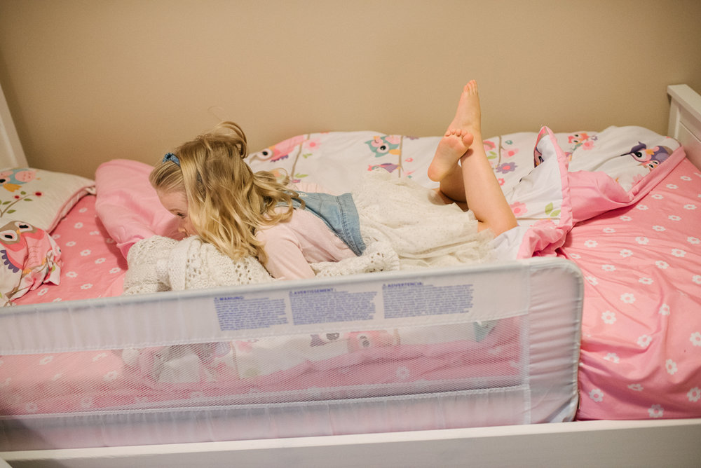 Young girl sleeping on her bed with pink blanket