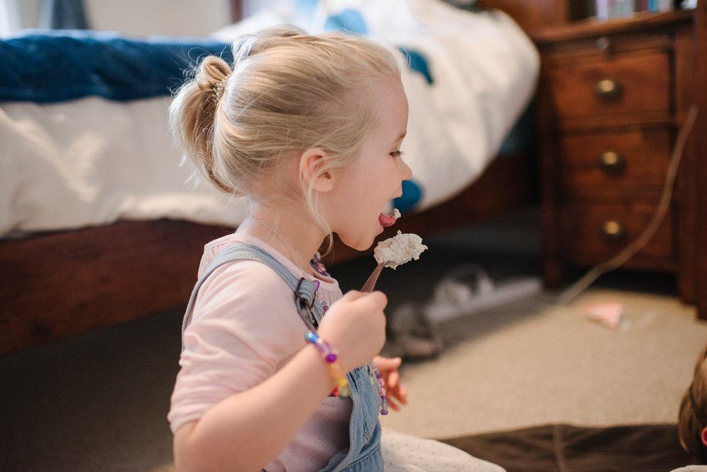 Girl licking food off of spoon