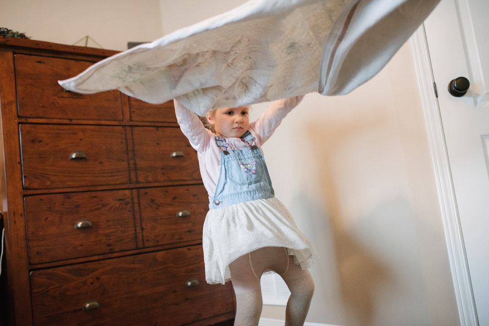 Girl playing with a blanket standing up