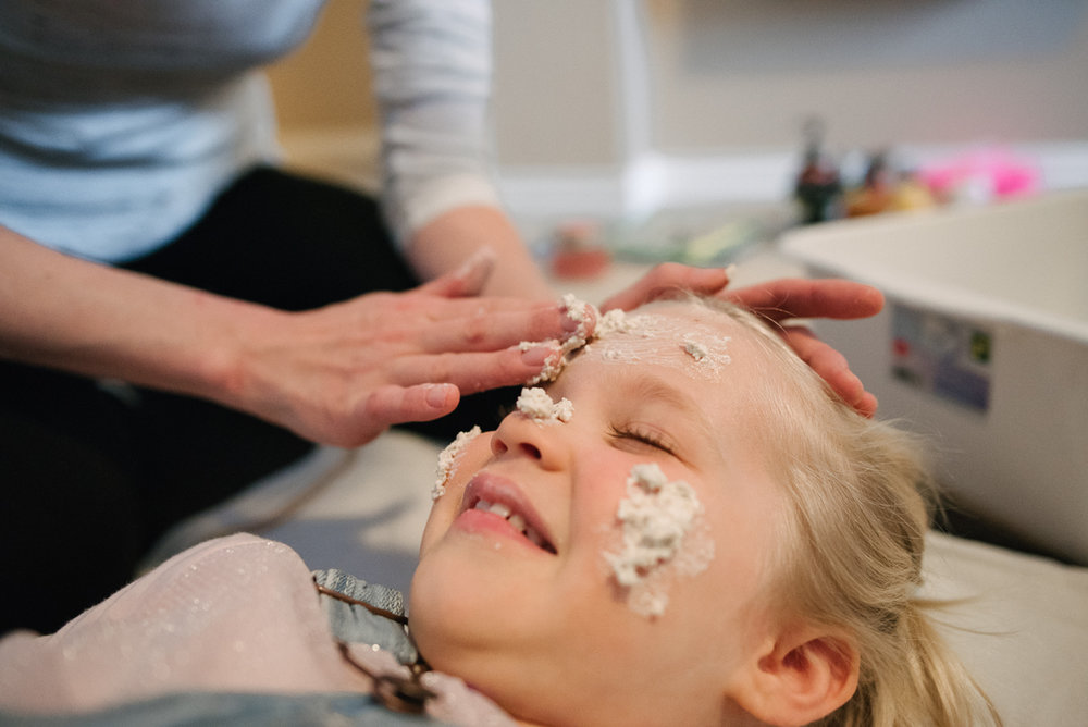 Daughter getting face treatement from mother