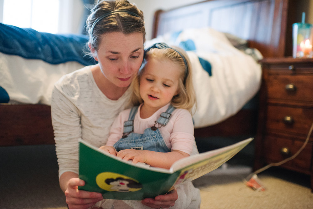 Mother and daughter reading a book next to bed