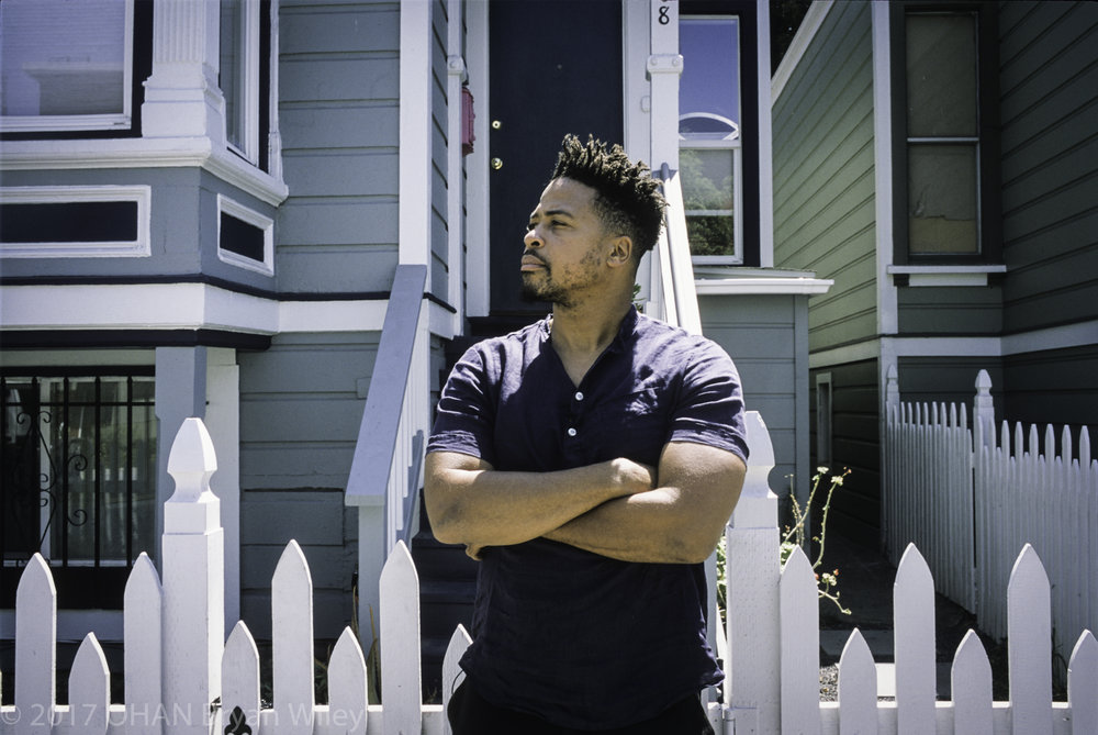 Zion I, a local and internationally known rapper, stands in front of his former home in Oakland's neighborhood known as the Lower Bottoms.