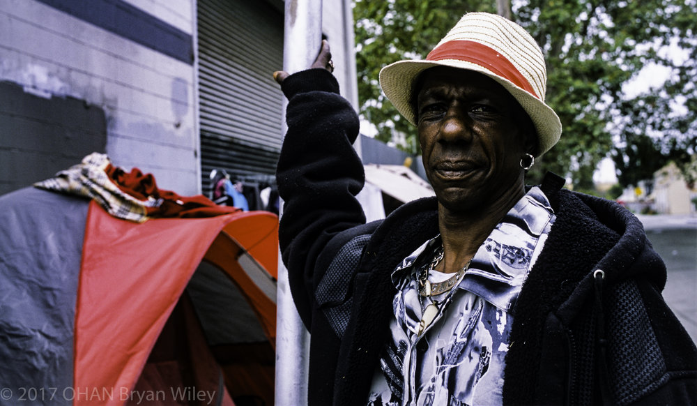 A homeless man that goes by his first name Bruce, says that his wife is a chef and makes 'good' money. They live in a tent in West Oakland because the lack of affordable housing in Oakland.