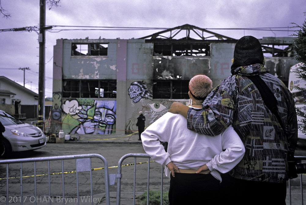 Two individuals stand across the street and mourn the loss of 36 individuals, mostly young artist, that died inside the warehouse fire known as 'Ghost Ship.'
