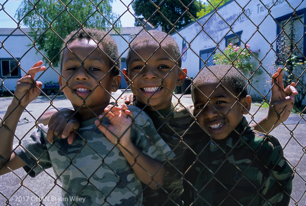 Students Arnel White, Aaron Hawkins, and Zachariah Christian, smile as they look through the fence of their school.  Pentecostal Way of Truth School has been a part of West Oakland since 1968 and has been serving the community by providing homes and refuge for the hungry and homeless.