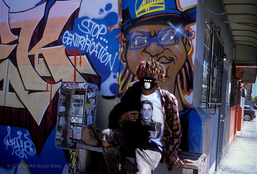 """A young Black male that goes by the name Sue, wears a face mask and Elvis tee-shirt as he sits next to a """"Stop Gentrification"""" sign in the Lower Bottoms of West Oakland."""