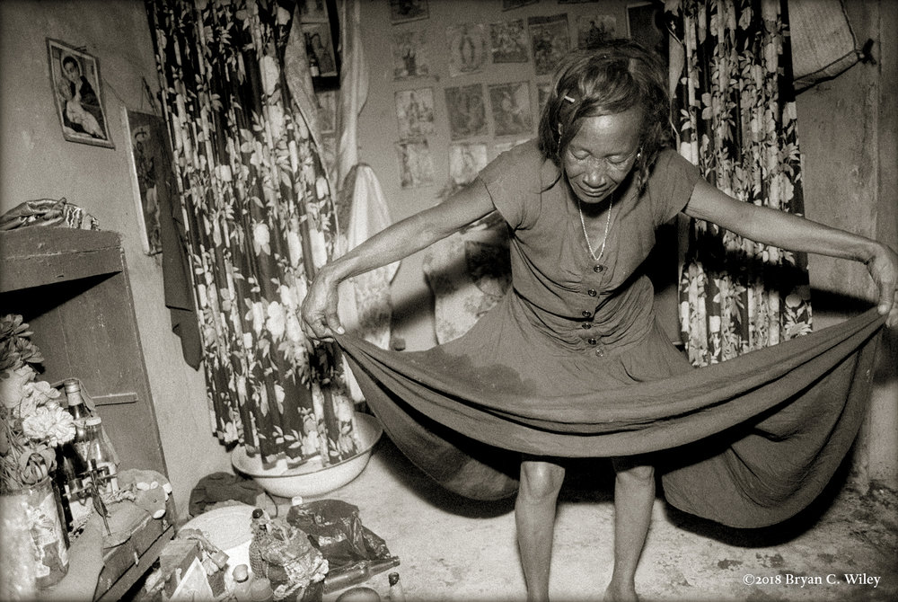 Vodousant bows to the spirits in her small sanctuary.  Gonaives, Haiti
