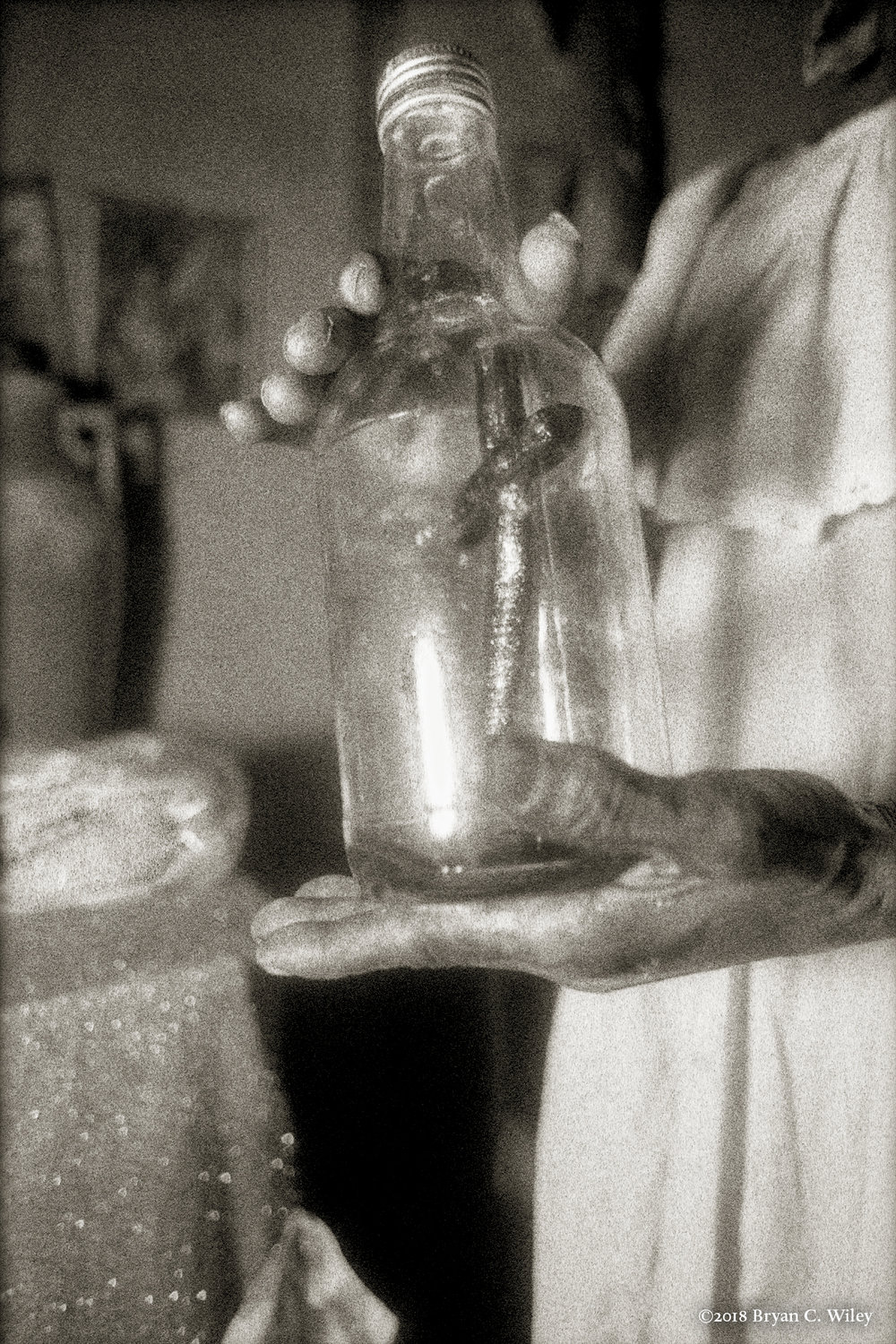 An old bottle of rum is now a sacred Vodou bottle held in the hands of a Hougan.  Sacred objects are often put into clear bottles to ward off evil spirits, or used as tools by priests.  Gonaives, Haiti