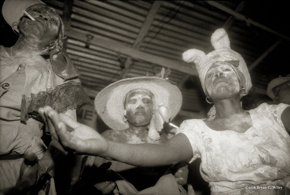 As if deceased, Servants of Gede appear white-faced.  Those possessed by the guardian of the Dead strut, thrust, dance, and laugh at the face of death throughout the temple, while drinking and smoking.  Gede mitigates the world between life and death, and Bawon Samdi is his supreme incarnation.  Gonaives, Haiti