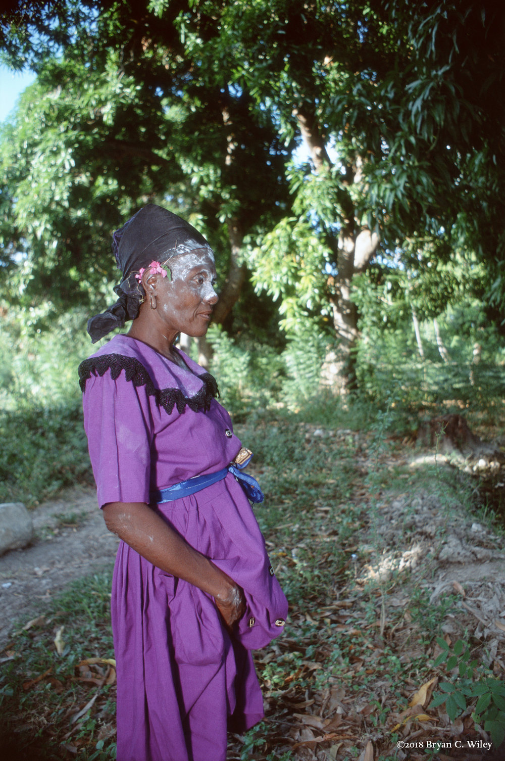 At an outdoor ceremony, the purple dress, large collar, and face covered in white like a corpse, imply this woman is a servant of Gede.  The Gede family are spirits of the dead representing the beginning and end of life.   Gonaives, Haiti