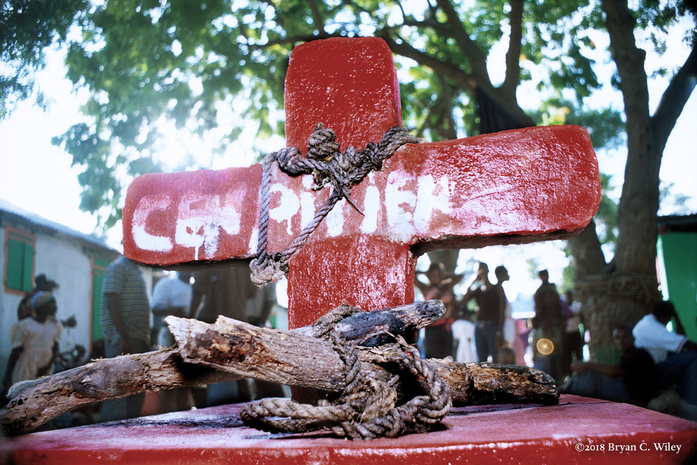 """In the ceremonial grounds outside a sanctuary, """"without pity"""" is painted on a Vodou cross covered with ropes and sacred objects.  Some objects are safeguards for the temple or used in magical acts.  Petit Goave, Haiti"""