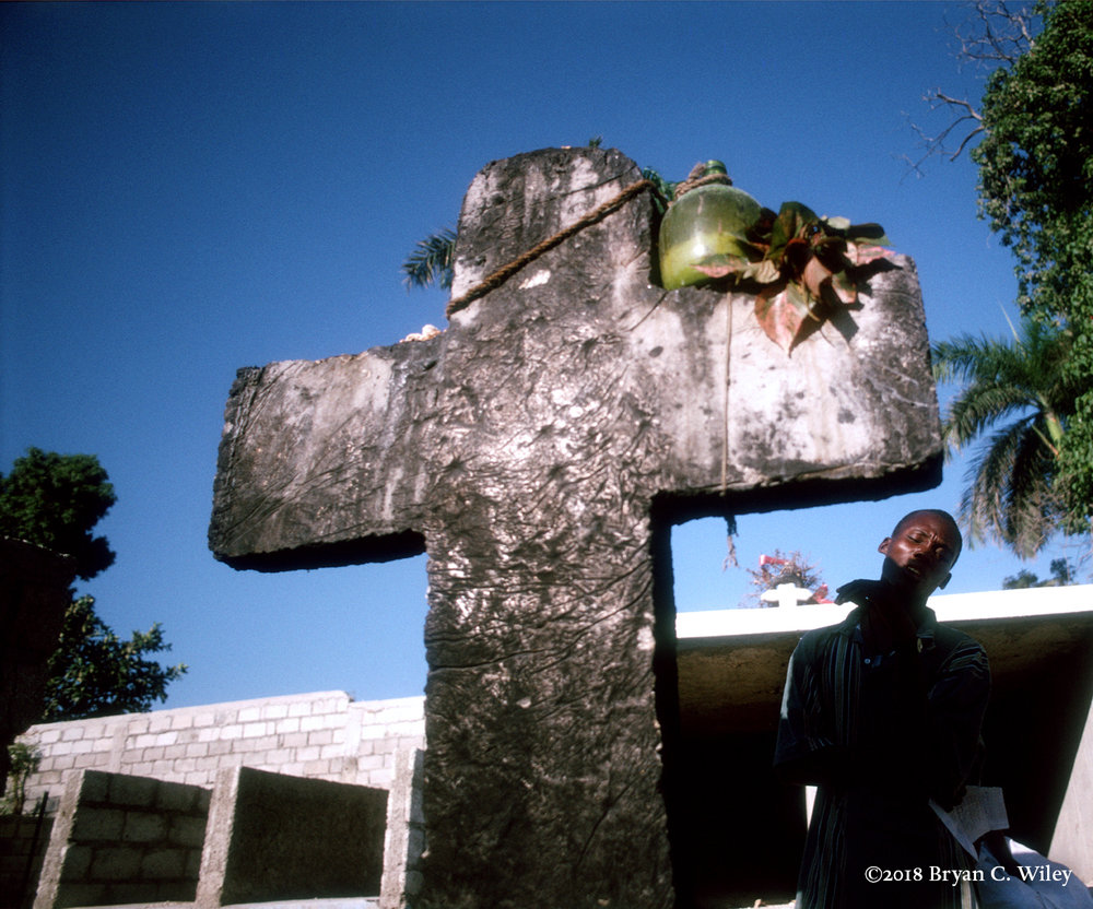 A young man prays at a Vodou cross adorned with offerings including a magic lamp.  Depending on the favor needed from the Vodou spirits, each magic lamp has specific ingredients and procedures for success.  The lamps must be placed on the altar dedicated to the guardian spirit.  Along with prayer, the lamp must be taken care of, not allowing the flame to die until the desired results are achieved.  Mirabalais, Haiti
