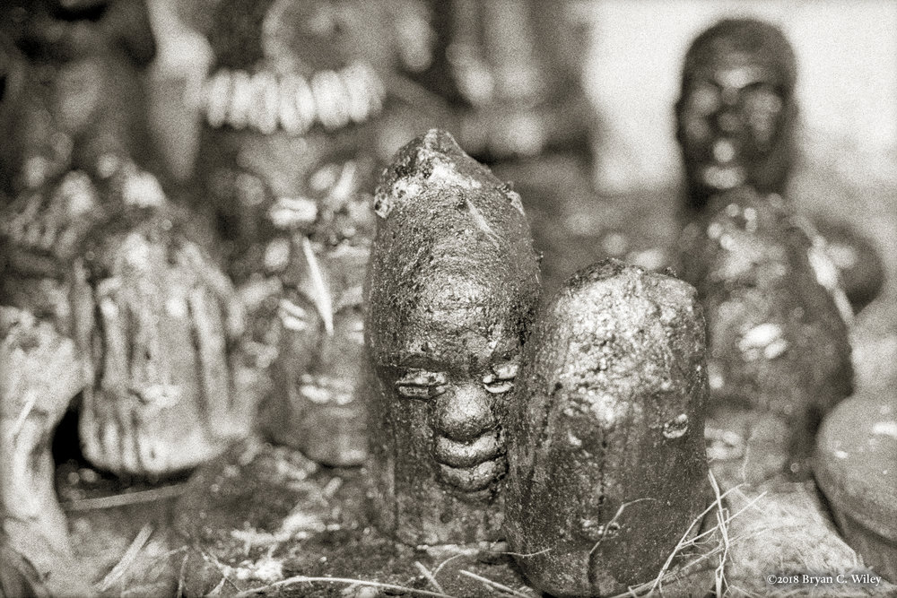 Figures molded of concrete and adorned with cowrie shells or carved from wood represent the deity Eleguá. Speaking through four pieces of coconut Eleguá has given permission for sacrifice to begin.  La Habana, Cuba