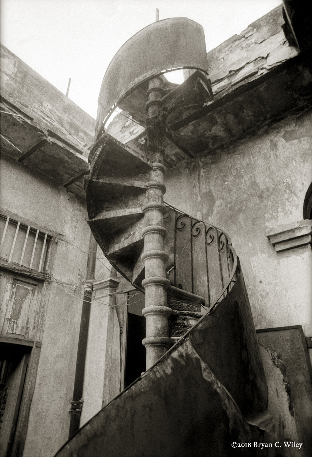 A staircase spirals from the patio of a Babalawo's multi-family home up to the second floor where more ceremonies take place. Its swirling stretch suggests the spiritual link–and actual DNA helix– that connect the New World with Africa.   La Habana, Cuba