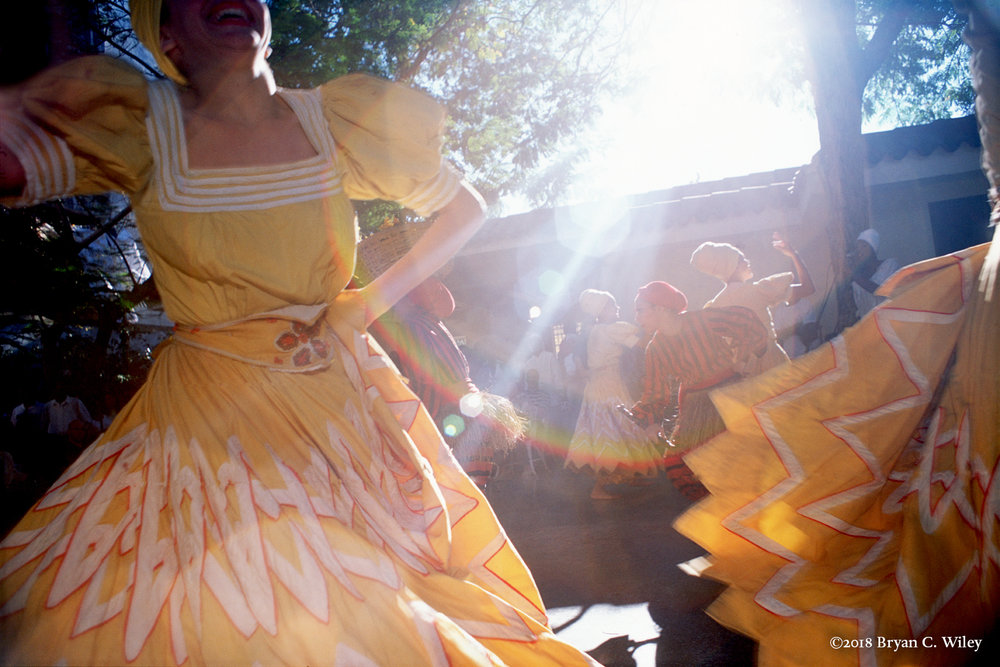Sunlight splashes in, casting a rainbow over dancers from Cuba's Conjunto Folklorico Nacional (National Folkloric Dance Troupe), Founded in 1962 to represent aspects of Cuba's rich African music and dance traditions on stage. They perform movements for the Elegua (the Yoruba/ Lucumi deity of crossroads and children, all clad in red and black) and for Ochun (the riverine goddess of love and creativity).  Elegua dances mischievously, brandishing his garabato like a wand, with which he opens up the possibilities of the crossroad. Ochun twirls and contemplates her Self in her hand, which represents a mirror, itself symbolic of the reflective surface of the river.  La Habana, Cuba