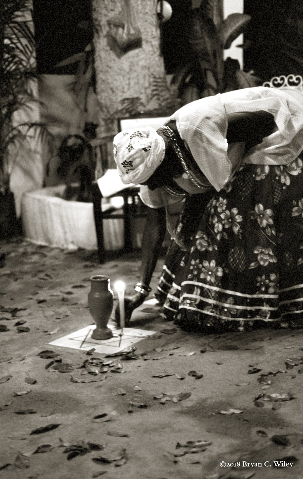 The Mae de Santo Noessa (mother of saints) starts the ceremony by lighting a candle and libations, pouring water to the earth. Sacred leaves called Ogbo cover the ground to attract the Orishas.   Cachoeira, Brazil