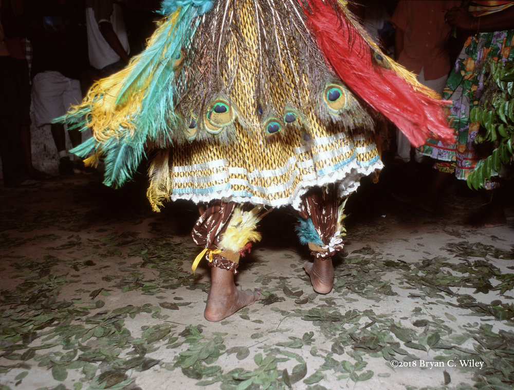 A Mae de Santo adorned in feathers at a Caboclo ceremony.  The Caboclos are a pantheon of deities worshipped in the Candombles of Bahia and throughout Brazil.  They are Brazilian cowboys and Indians feted at public parties and private ceremonies and invoked by devotees to work on earth.  Senhor do Bonfim, Brazil