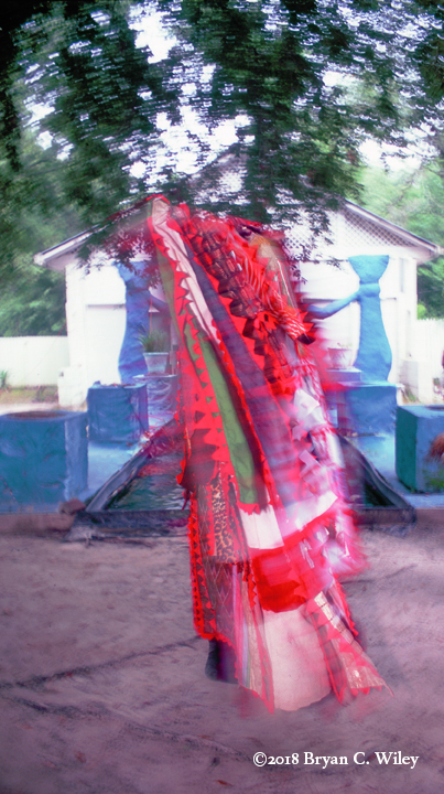 Egungun dancing as if floating in front of  Olokun Temple.  Oyotunji African Village, SC