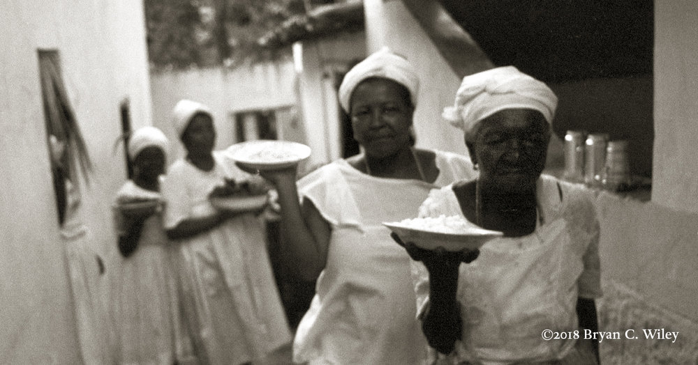Devotees carry food offerings to a sacred room for the Orisha Yemanja, goddess of the oceans.  Cachoeira, Brazil