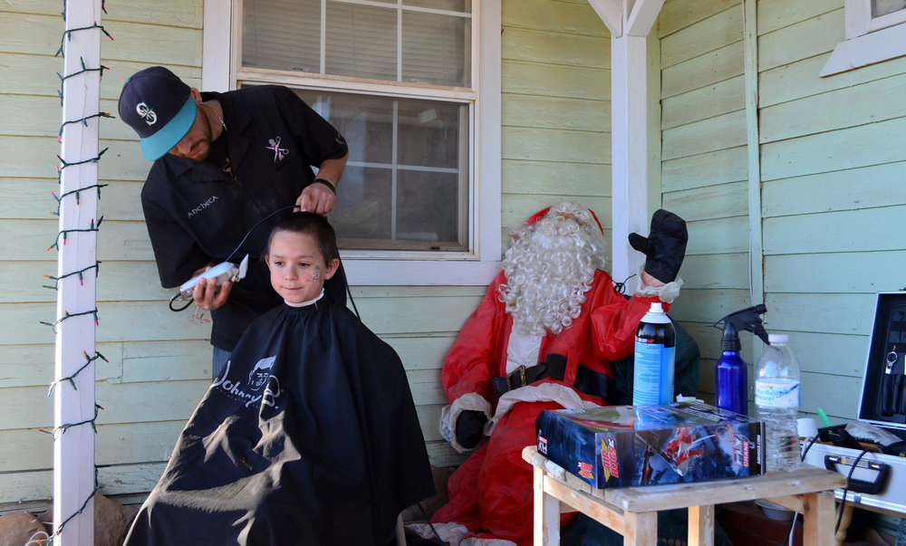DJ Ancheta gives Sky Broyles a haircut at the Forgotten Angels Christmas party in Niland. (Imperial Valley Press/Antoine Abou-Diwan)
