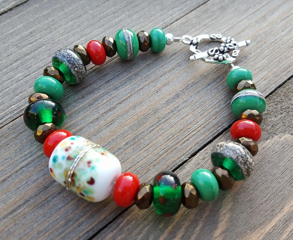 "Forest Lights bracelet by Kemberly Mills. ""Gorgeous Christmas-themed bracelet with a forest-like feel.""  Silvered focal & green/red dot beads by Sheri Fisher.  Silvered transparent green beads by Francesca DeCaire . Silvered green beads & red and green spacers by Cheryl Harris."