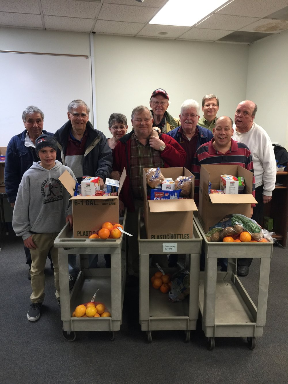 Our team with 3 complete food baskets ready for delivery.  Over the years we have provided more than 3,200 food baskets to our local community through the St. Joseph Catholic Church' Food Pantry.