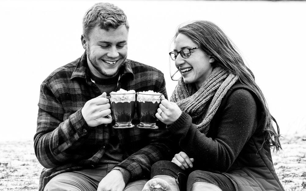 Couple clinking hot cocoa mugs