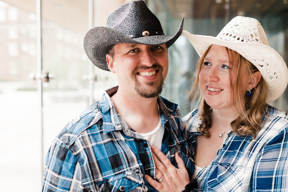 Engagement photo of couple wearing cowboy hats and plaid shirts at the Chazen Museum of Art in Madison, WI.