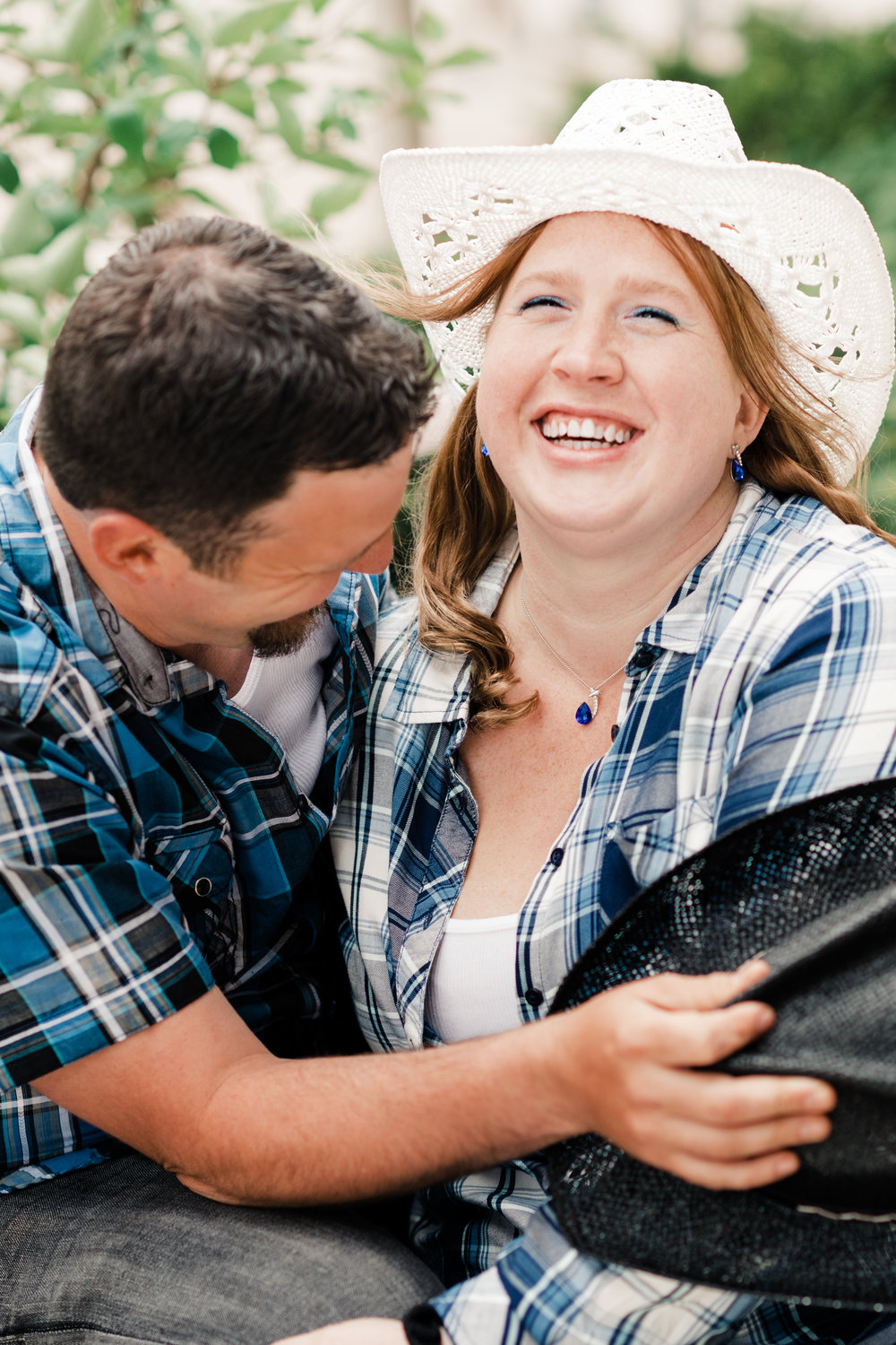 Engagement photo of couple laughing and wearing cowboy hats and plaid shirts at the Chazen Museum of Art in Madison, WI.