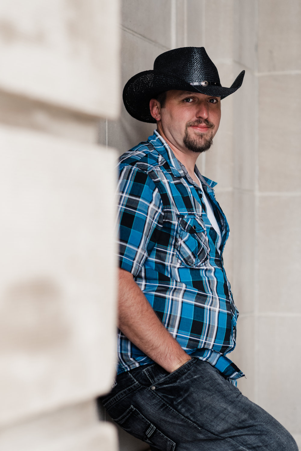 Engagement photo of a groom with his back to the wall, looking at the camera, and wearing cowboy hats and plaid shirts at the Chazen Museum of Art in Madison, WI.