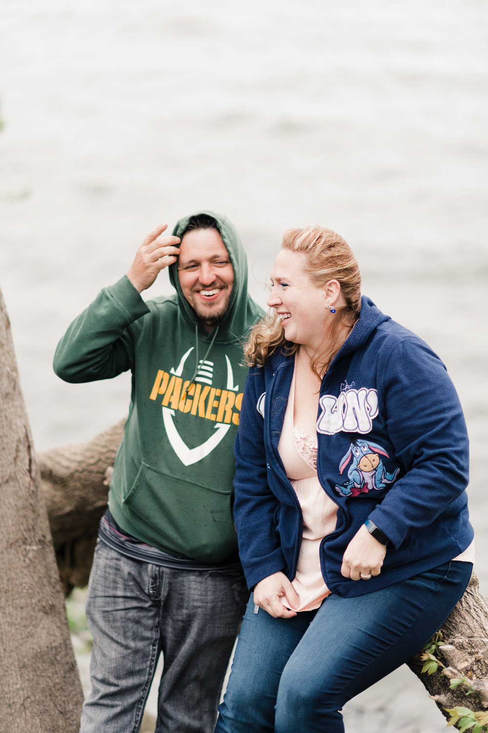 Engagement photo of a couple laughing and sitting on a tree branch in front of Lake Mendota at James Madison Park in Madison, WI.