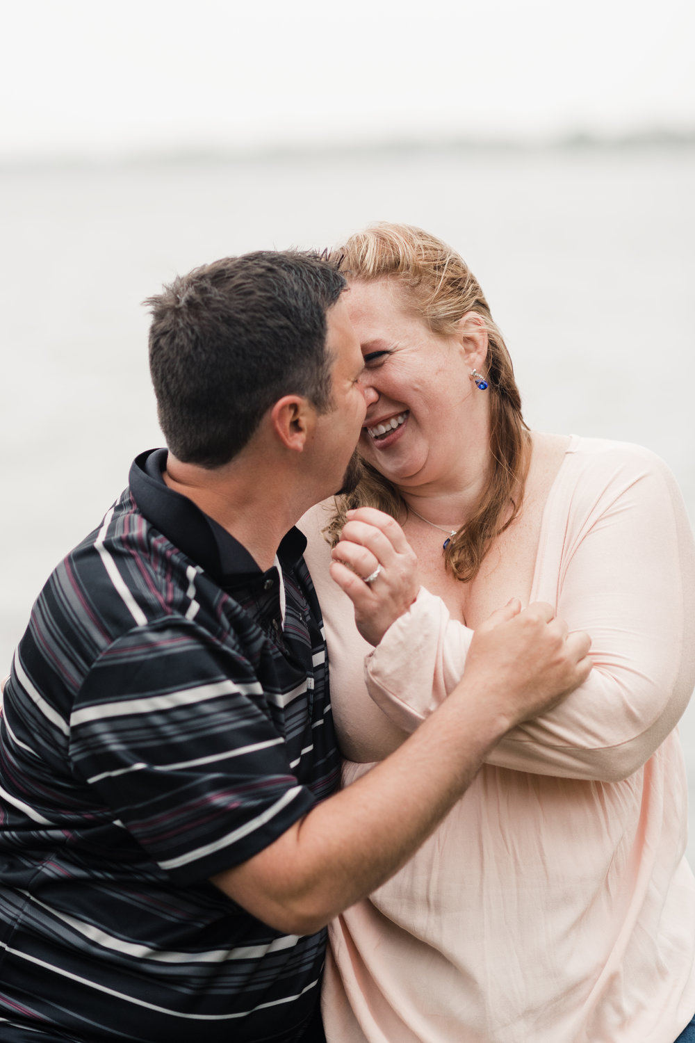 Engagement photo of a couple laughing and holding each other in front of Lake Mendota at James Madison Park in Madison, WI.