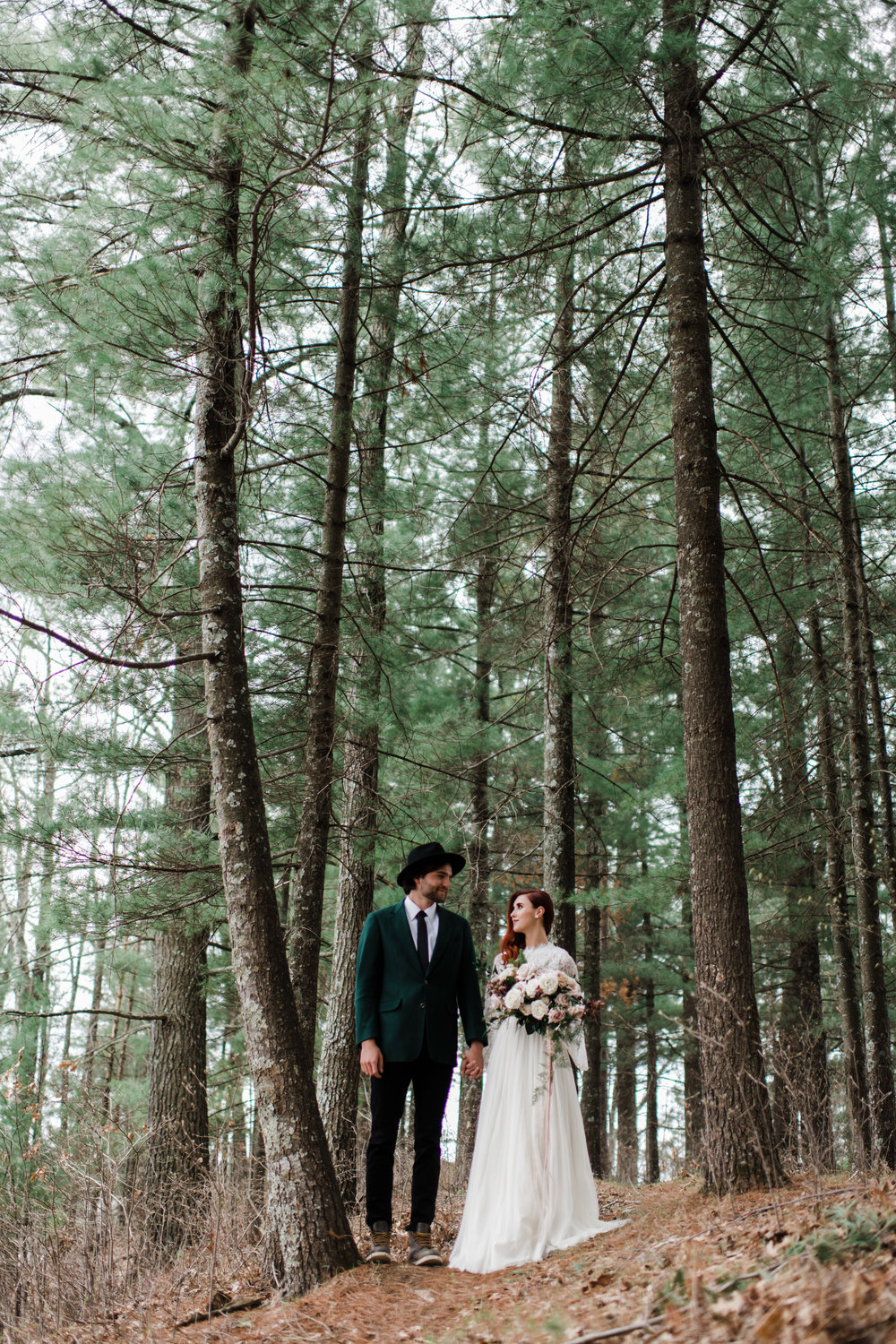 Couple wearing wedding attire holding hands and looking into each other's eyes in the Northwoods of Wisconsin.