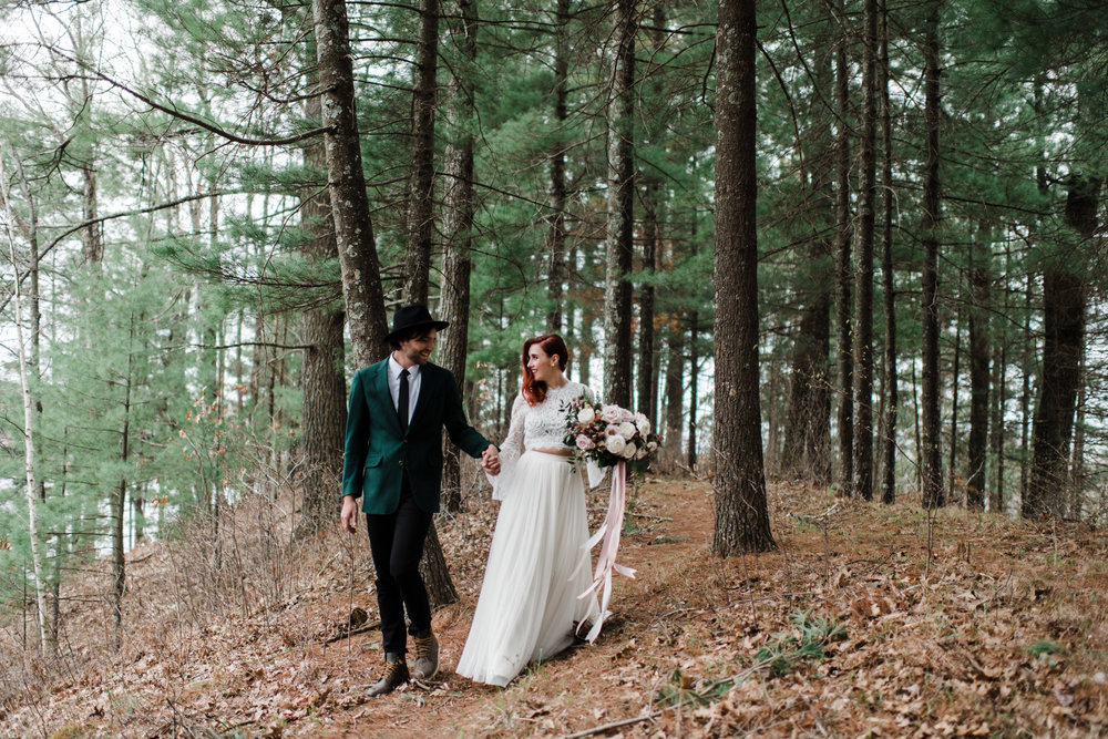 Couple wearing wedding attire walking and holding hands in the Northwoods of Wisconsin.