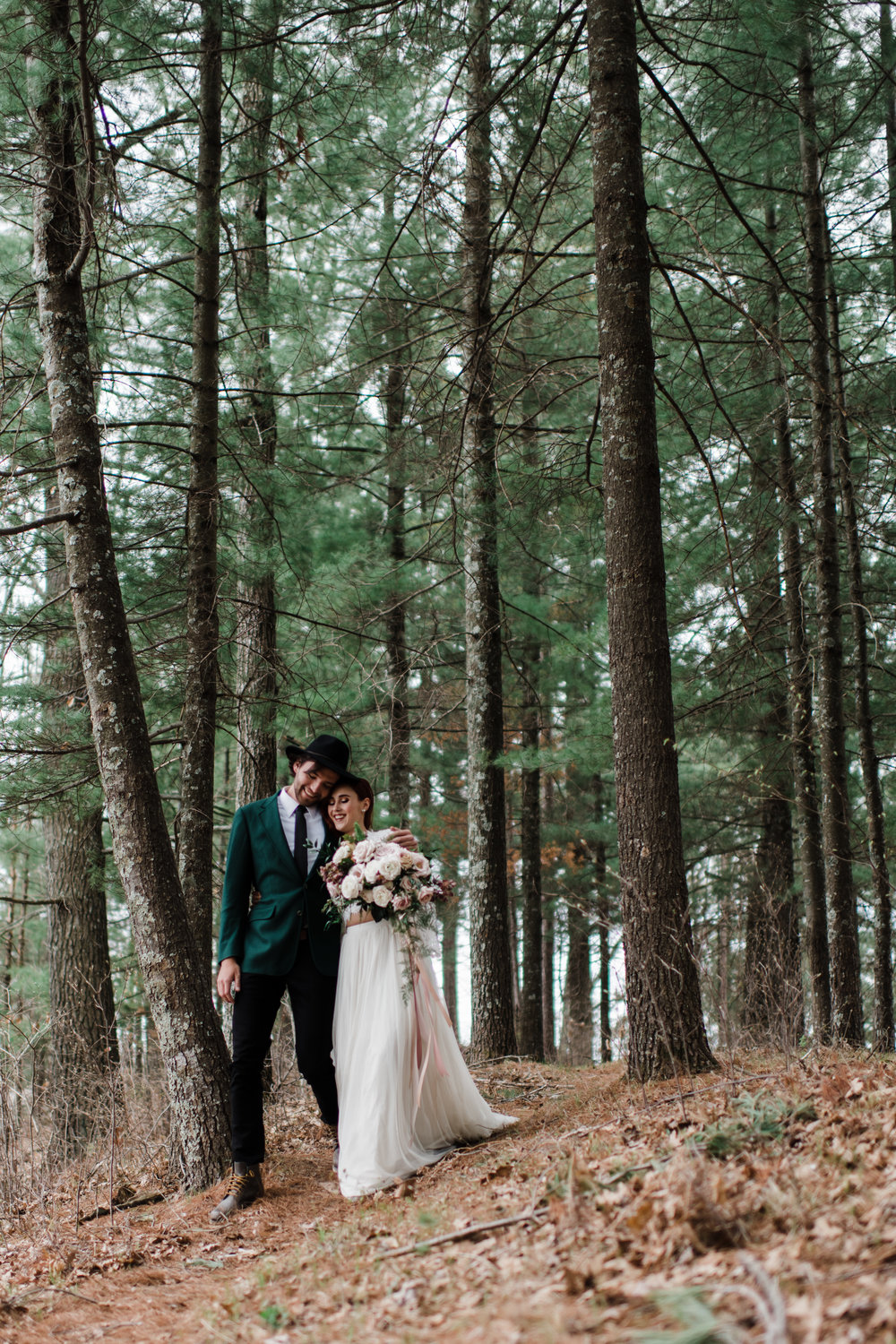 Couple wearing wedding attire walking with arms around each other in the Northwoods of Wisconsin.