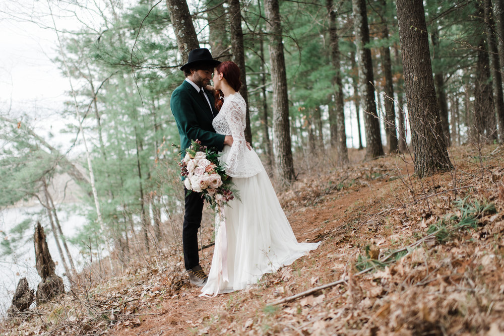 Couple wearing wedding attire gazing into each other's eyes in the Northwoods of Wisconsin.