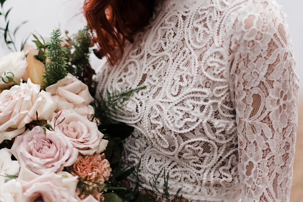 Bride wearing lace and beaded crop top holding a bouquet of flowers.