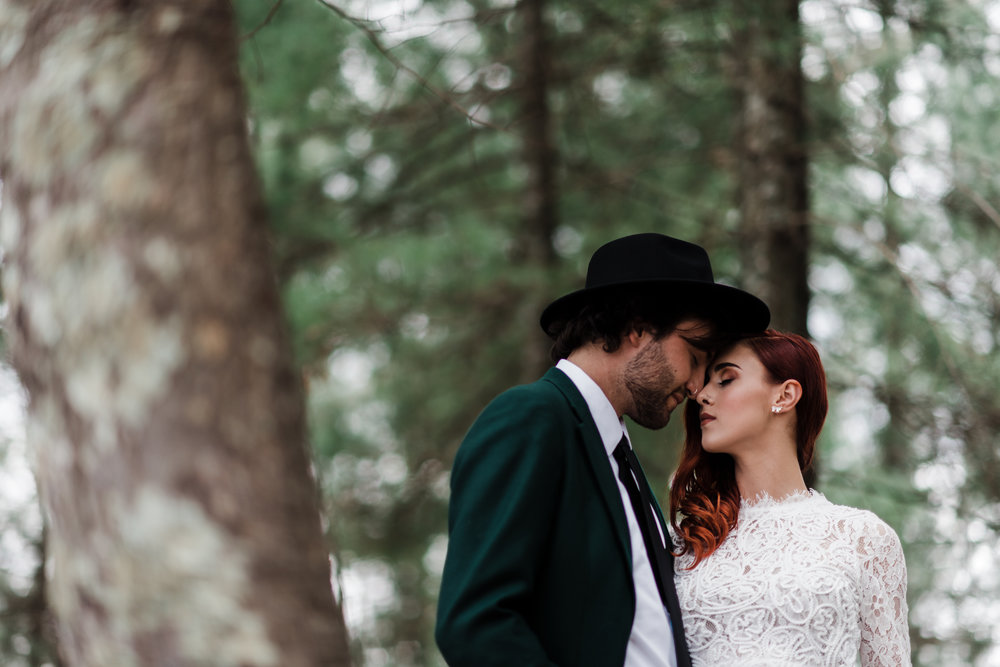 Groom in green jacket and black fedora and bride in lace and beaded crop top forehead to forehead with eyes closed.