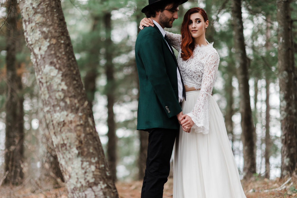Groom in green jacket and black fedora slow dancing in the woods with bride in lace and beaded crop top and flowing skirt.