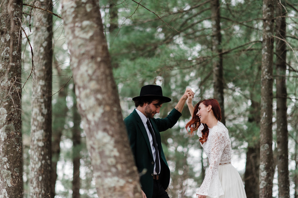 Groom in green jacket and black fedora and bride in lace and beaded crop top and flowing skirt laughing in the Northwoods of Wisconsin.