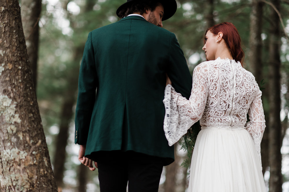Groom in green jacket and black fedora walking in the Northwoods of Wisconsin with bride in lace and beaded crop top and flowing skirt.