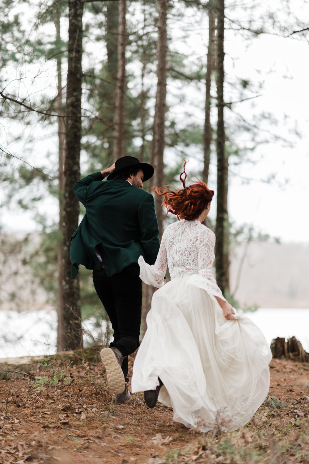 Groom in green jacket and black fedora running in the Northwoods of Wisconsin with bride in lace and beaded crop top and flowing skirt.